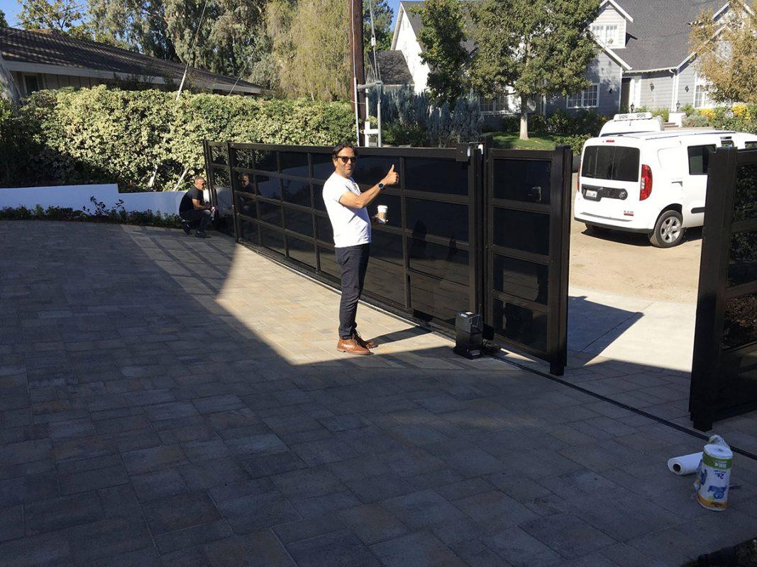 Team working on black glass driveway gate