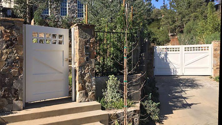 White hillside driveway gate and entry gate