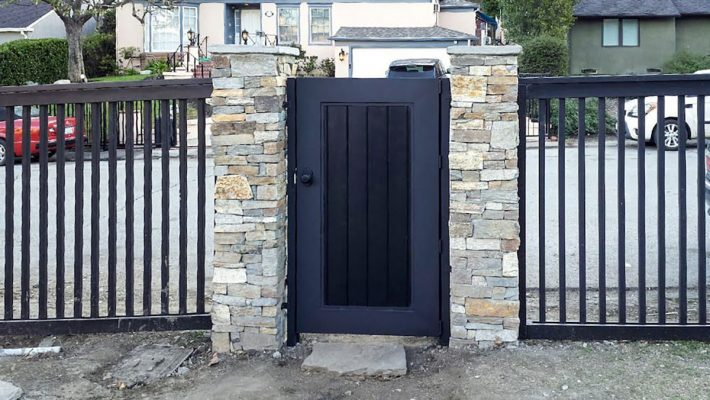 Black wood entry gate with side fencing